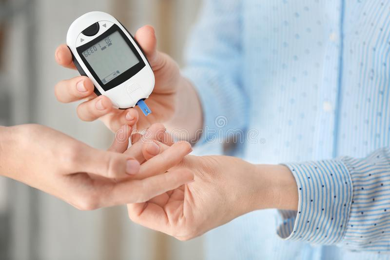 Doctor checking diabetic patient`s blood sugar level. With digital glucometer, closeup royalty free stock photography