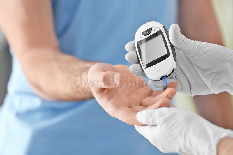 Doctor checking diabetic patient`s blood sugar level royalty free stock photos