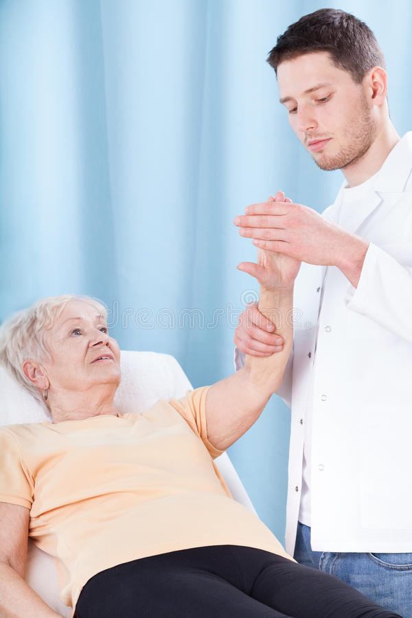 Doctor checking elderly patient's arm stock images