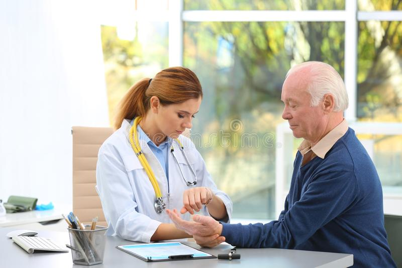 Doctor checking elderly patient`s pulse stock photography