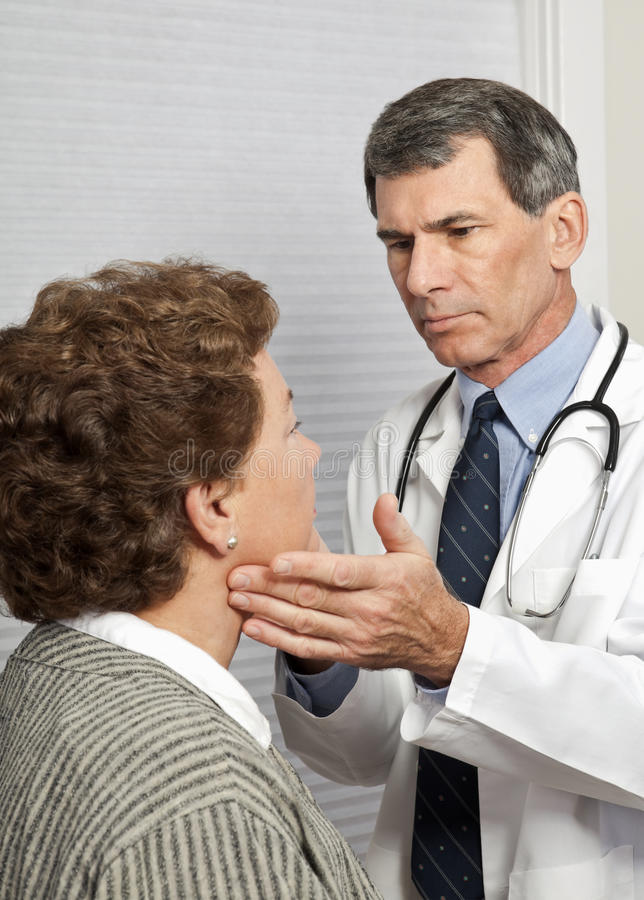 Doctor Checking Female Patient For Flu Symptoms stock images