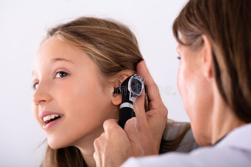 Doctor Checking Girl`s Ear royalty free stock photography