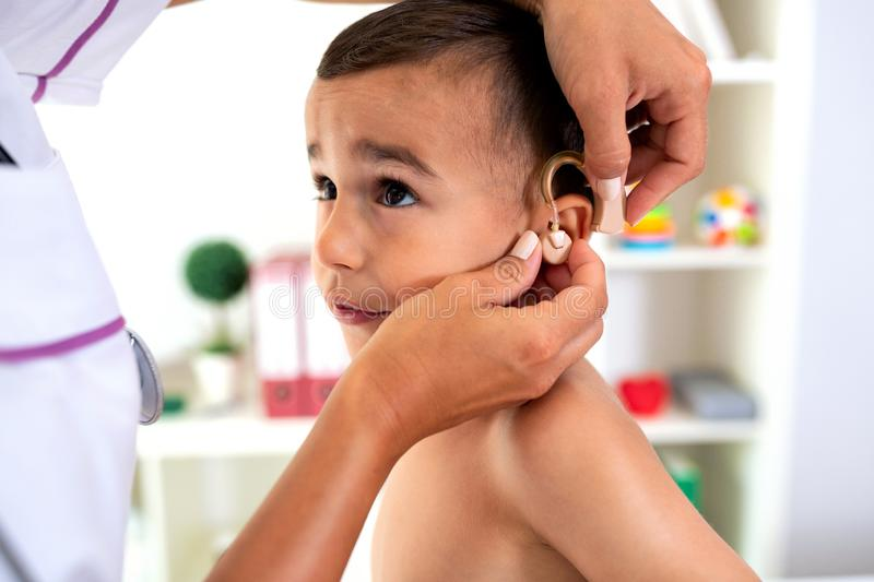 Doctor checking hearing aid device royalty free stock image