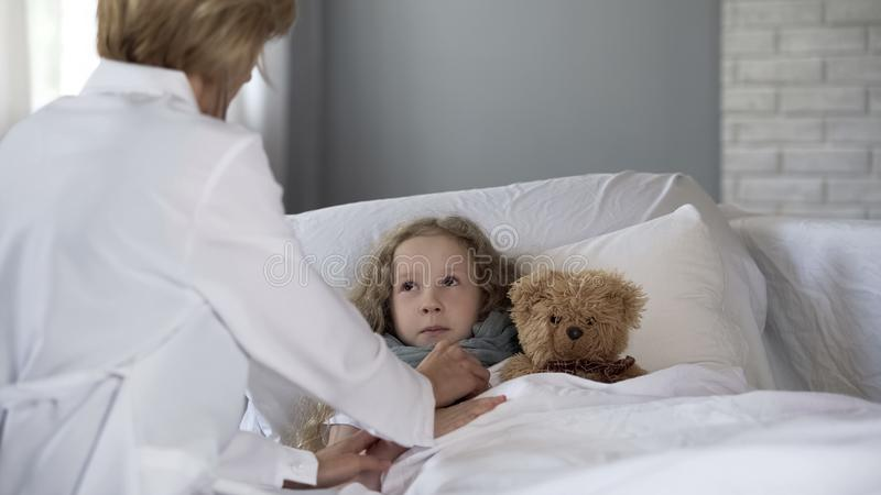 Doctor checking heart and lungs of scared girl with stethoscope in hospital royalty free stock photo
