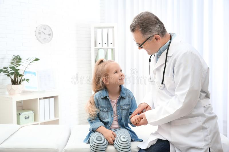Doctor checking little girl`s pulse with fingers in hospital. Space for text royalty free stock image