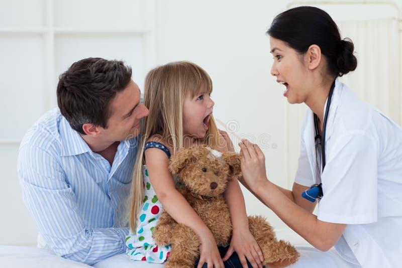 Doctor checking little girl's throat stock image