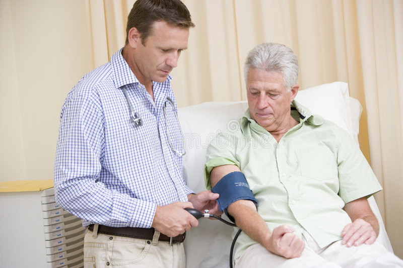 Doctor checking man's blood pressure royalty free stock photography