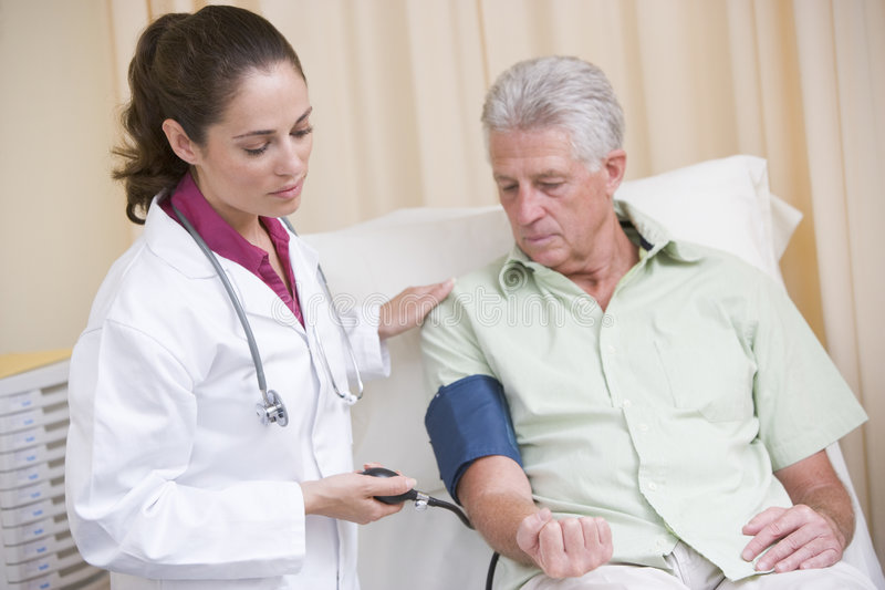 Doctor checking man's blood pressure in exam room stock images