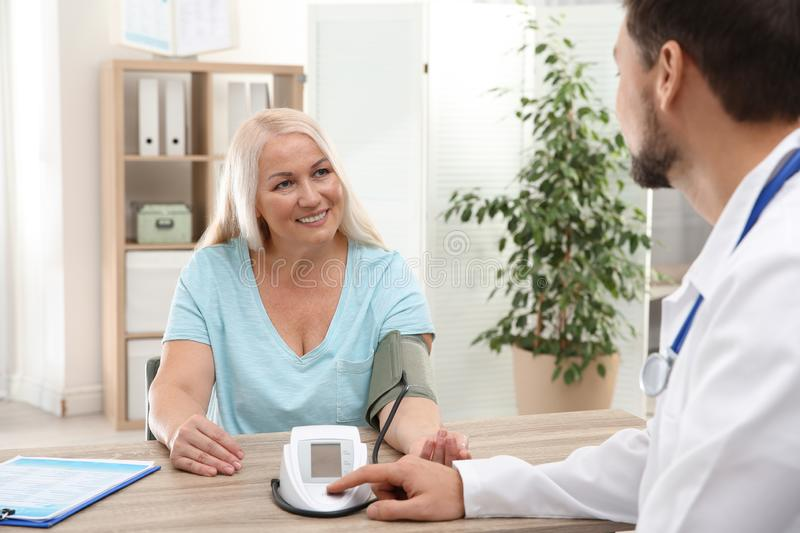 Doctor checking mature woman`s pulse with medical device royalty free stock photo