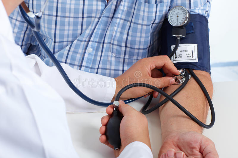Doctor checking patient blood pressure. stock photos