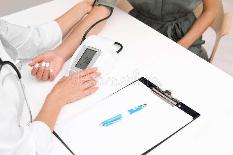 Doctor checking patient`s blood pressure at table royalty free stock image