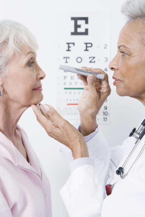Doctor Checking Patient's Eye. Senior female doctor checking patient's eye using testing instrument in clinic royalty free stock photography