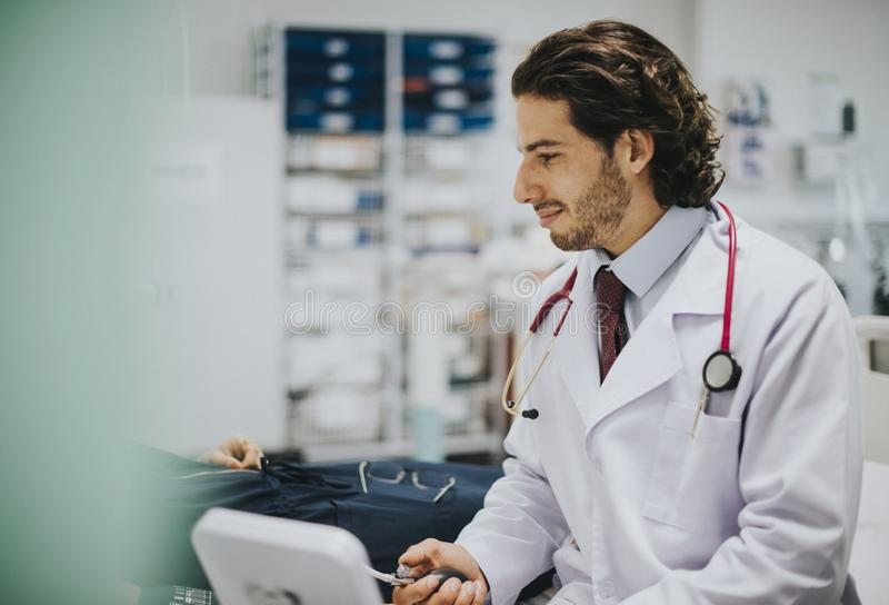 Doctor checking a patients blood pressure stock photos