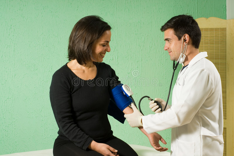 Doctor Checking Patients Blood Pressure - horizont. A young doctor, standing, checking his patient's blood pressure, while sitting. - horizontally framed stock photos
