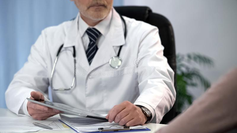 Doctor checking patients data on tablet, keeping medical records, consultation royalty free stock photography