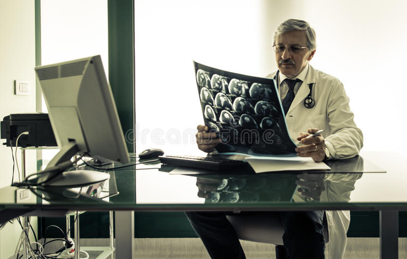 Doctor checking the x-ray test in his office royalty free stock image