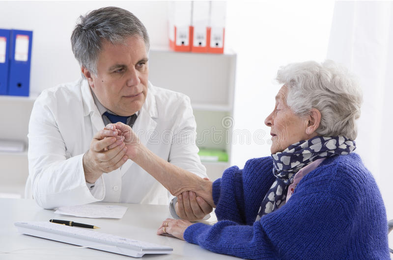 Doctor checking senior female patient's injured arm stock photography