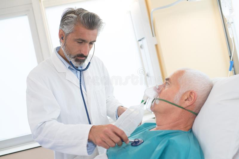 Doctor checking on senior patient heart rate royalty free stock photo