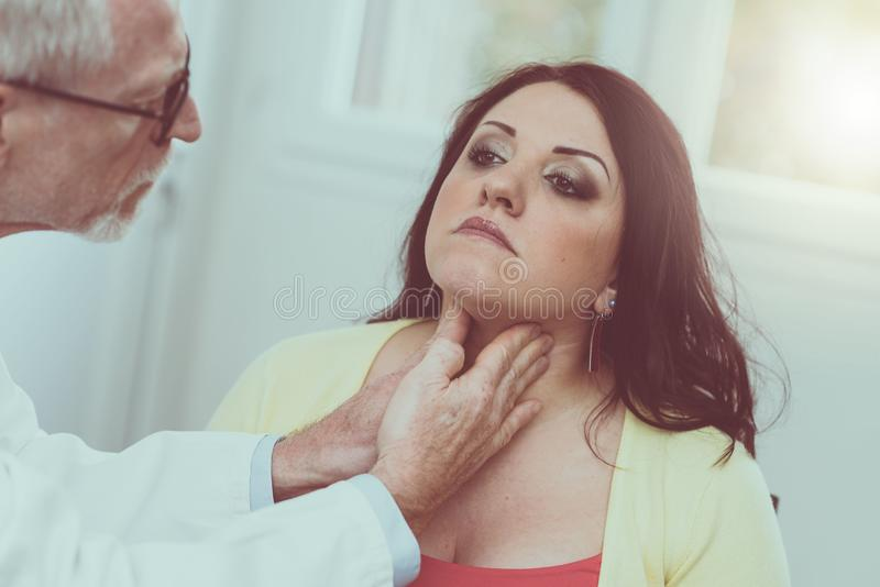 Doctor checking thyroid. Of a young patient stock photo
