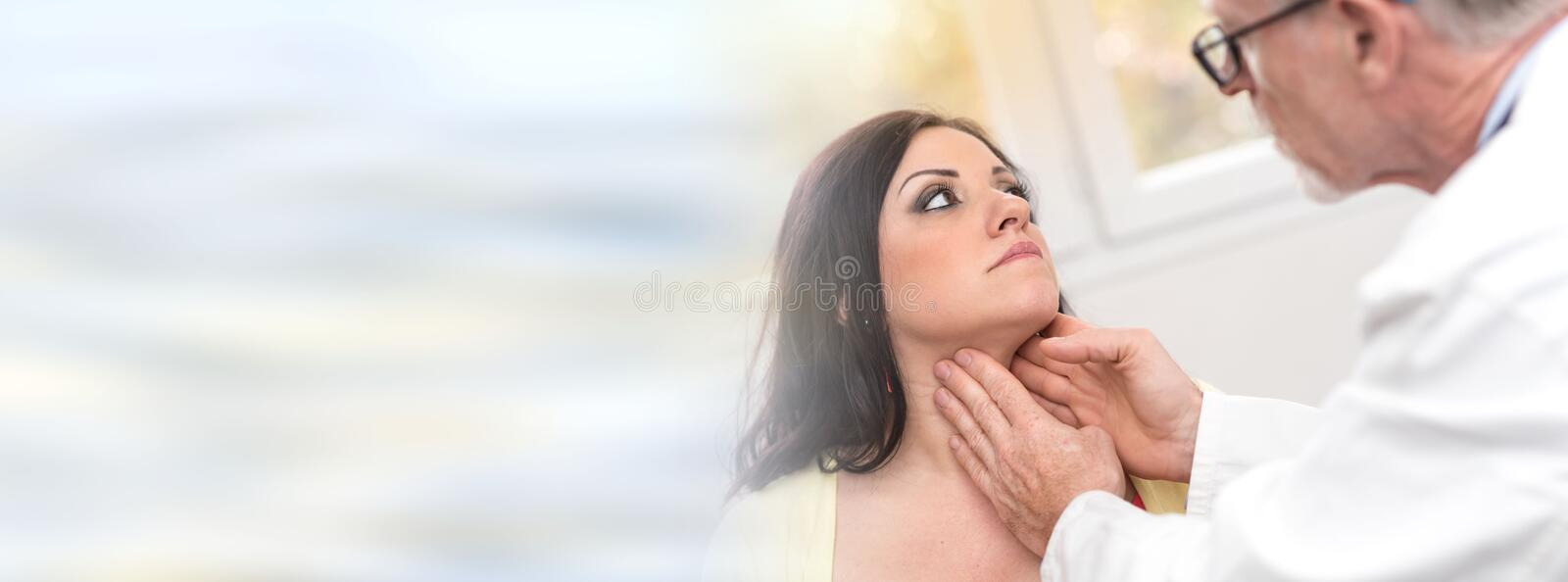 Doctor checking thyroid. Of a young patient royalty free stock image
