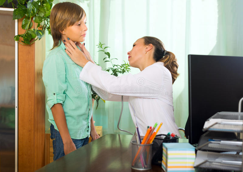 Doctor checking thyroid of teenager. Female doctor examining thyroid of teenage boy patient in clinic royalty free stock photography