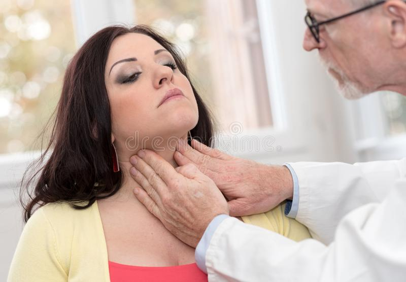 Doctor checking thyroid. Of a young patient stock photography