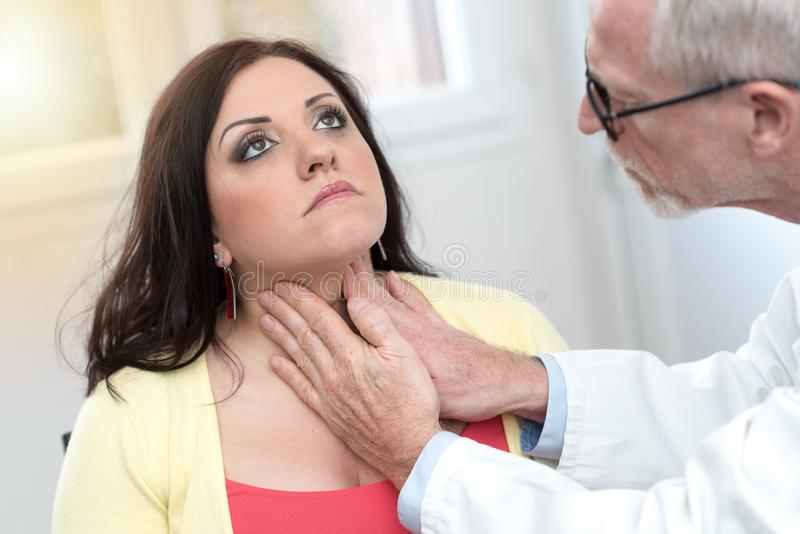 Doctor checking thyroid, light effect. Doctor checking thyroid of a young patient, light effect royalty free stock photography