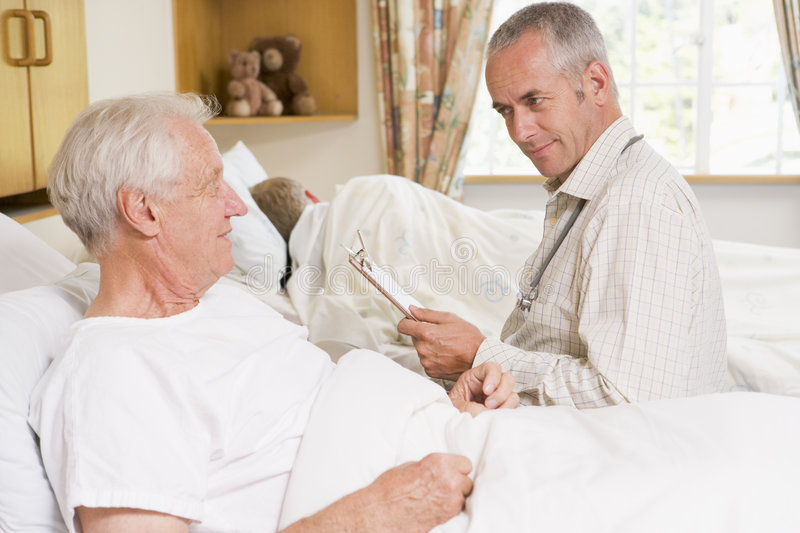 Doctor Checking Up On Senior Man In Hospital stock image
