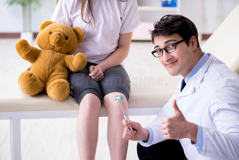 The doctor checking up young girls reflexes with hammer. Doctor checking up young girls reflexes with hammer royalty free stock image