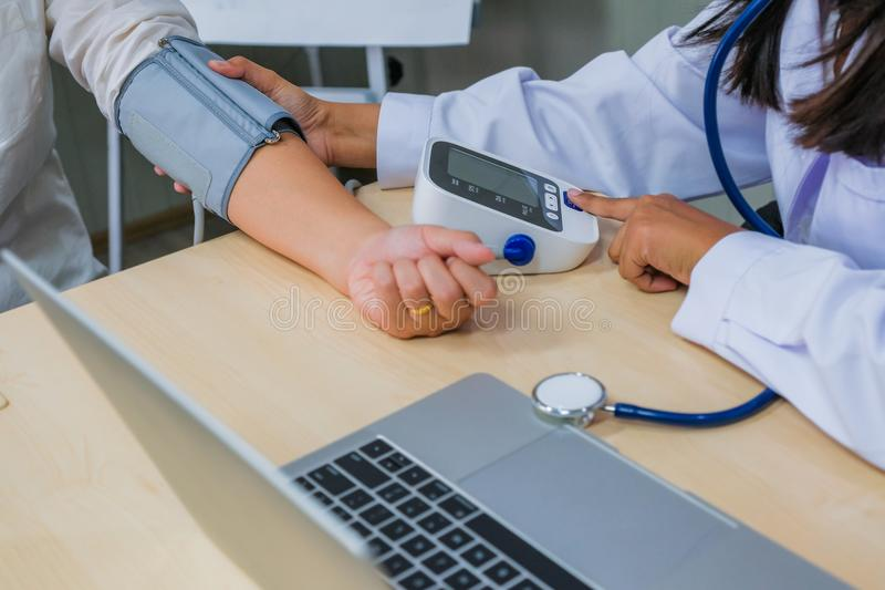 Doctor checking woman patient arterial blood pressure. Health c stock images