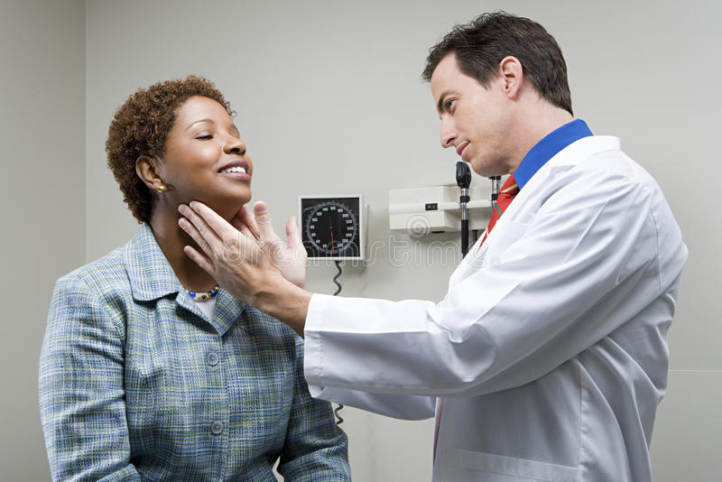 Doctor checking womans throat royalty free stock image