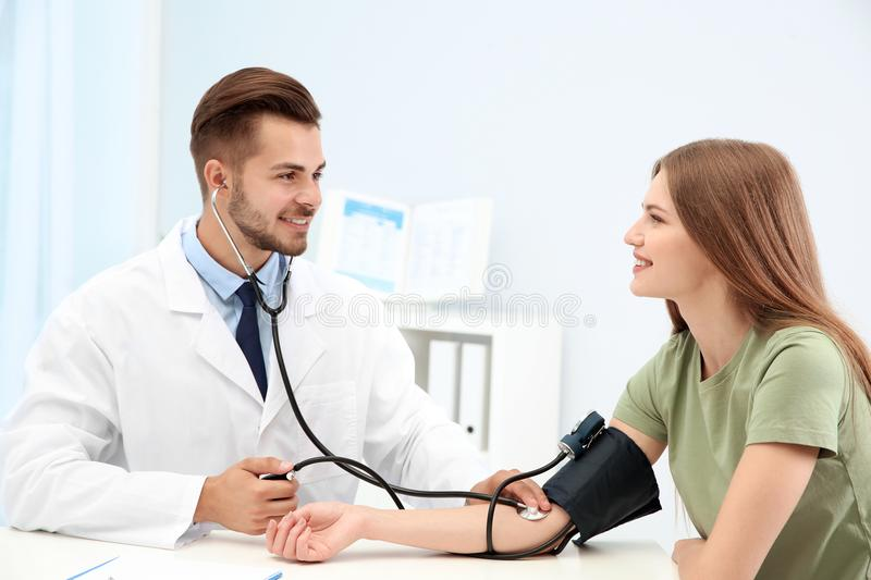 Doctor checking young woman`s pulse stock photography