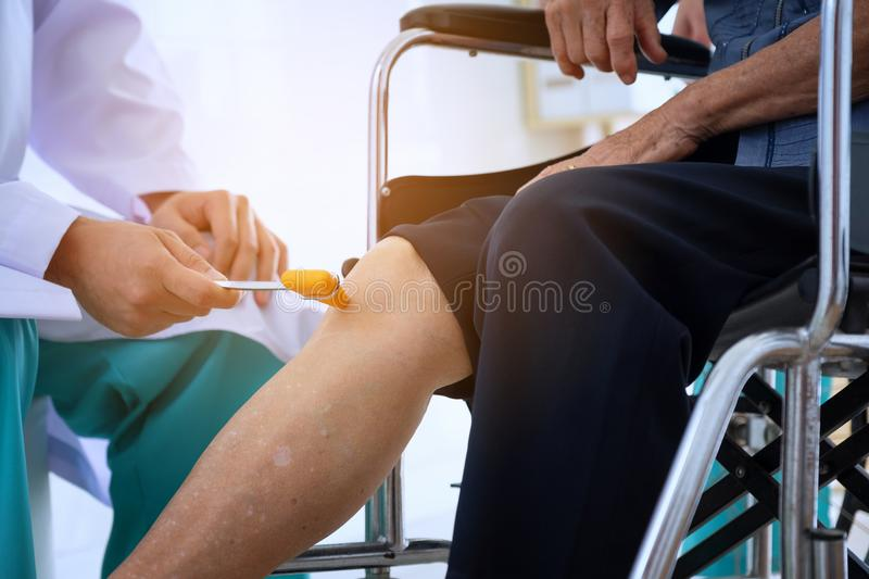 Doctor checks the patient`s reflexes. Neurologist Hammer for kno royalty free stock photos