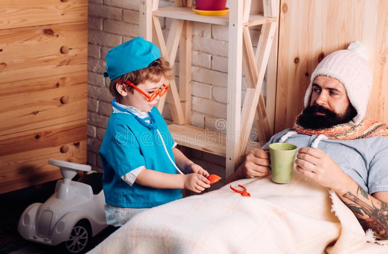 Doctor child in glasses with stethoscope examine father at home Doctor boy in doctor uniform treat patient, game and. Doctor child in glasses with stethoscope royalty free stock photos