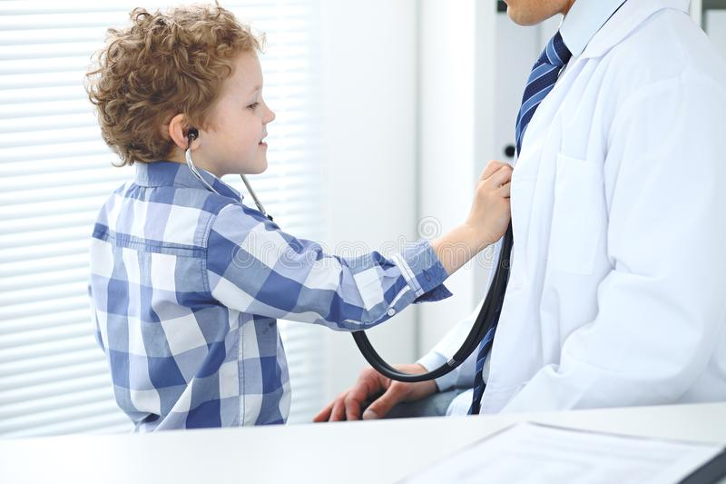 Doctor and child patient. Little boy play with stethoscope while physician communicate with him. Children`s therapy and royalty free stock photography