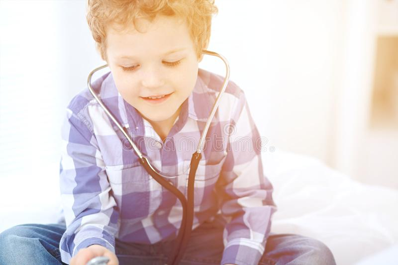 Doctor and child patient. Little boy play with stethoscope while physician communicate with him. hildren`s therapy and. Trusting relationship in medicine stock images
