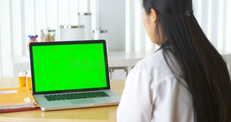 Doctor chino que habla con el ordenador portátil con la pantalla verde fotos de archivo