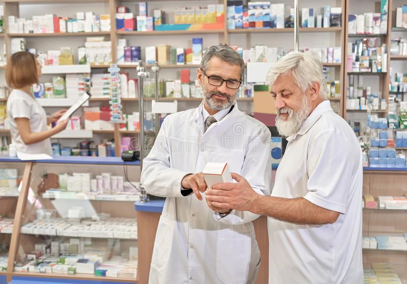 Doctor helping pansioner with choice of medicines. royalty free stock photo