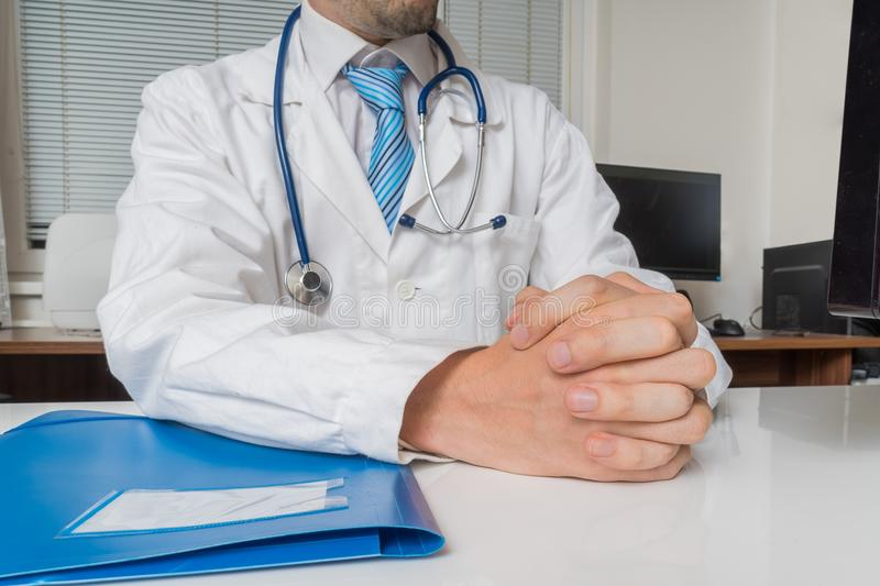 Doctor with clasped hands is listening. Expertise consultation concept.  stock images