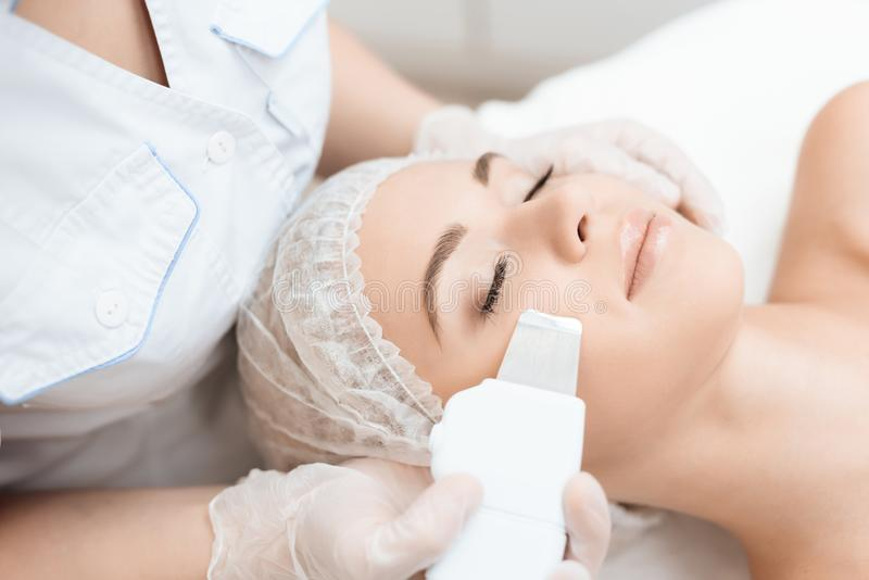 The doctor cleanses the woman`s skin with a special medical device. The woman came to procedure of laser hair removal. The doctor cleanses the woman`s skin with stock photos