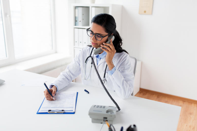 Doctor with clipboard calling on phone at hospital. Medicine, people and healthcare concept - female doctor with medical report on clipboard calling on phone at royalty free stock photography