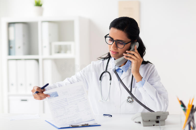 Doctor with clipboard calling on phone at hospital stock photography