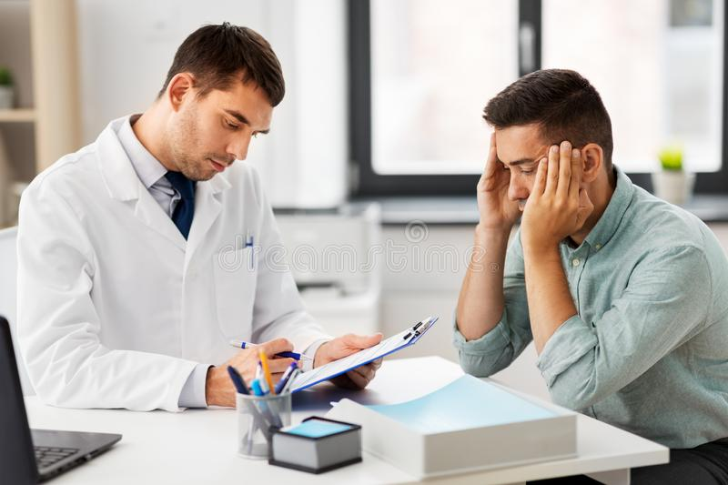 Doctor with clipboard and male patient at hospital royalty free stock photos