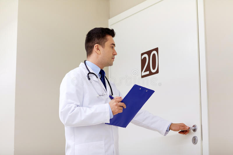 Doctor with clipboard opening hospital ward door. Clinic, people, health care and medicine concept - doctor with clipboard opening hospital ward door stock photos