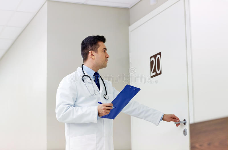Doctor with clipboard opening hospital ward door. Clinic, people, health care and medicine concept - doctor with clipboard opening hospital ward door royalty free stock photo