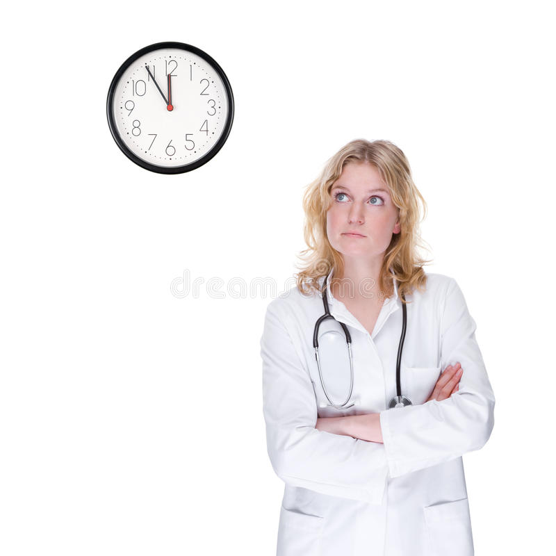 Doctor with clock. Full isolated portrait of a beautiful caucasian doctor looking at the clock royalty free stock photo