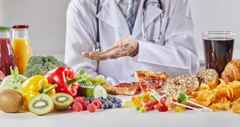 Doctor in coat comparing good and bad food. One including bread and chips, other including fruits and vegetables stock image