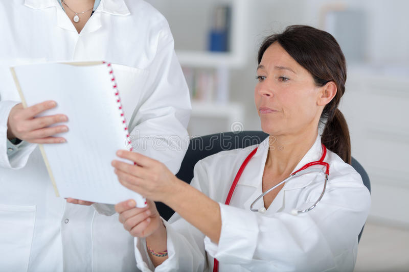 Doctor with colleague sharing points views stock images