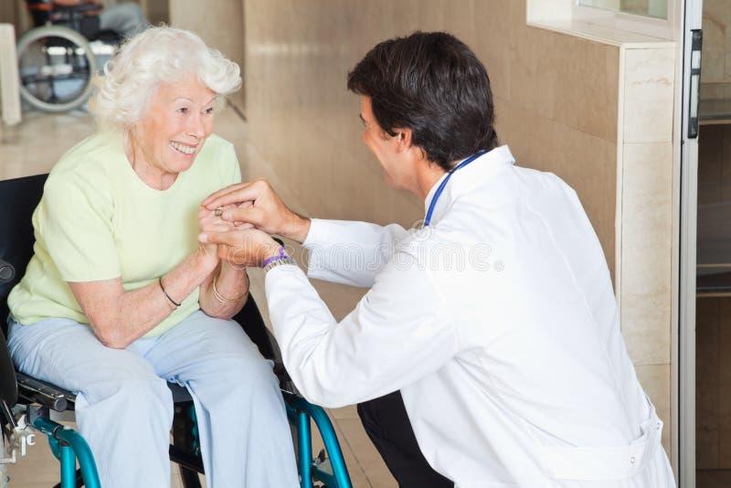 Doctor Comforting Happy Senior Woman stock photo