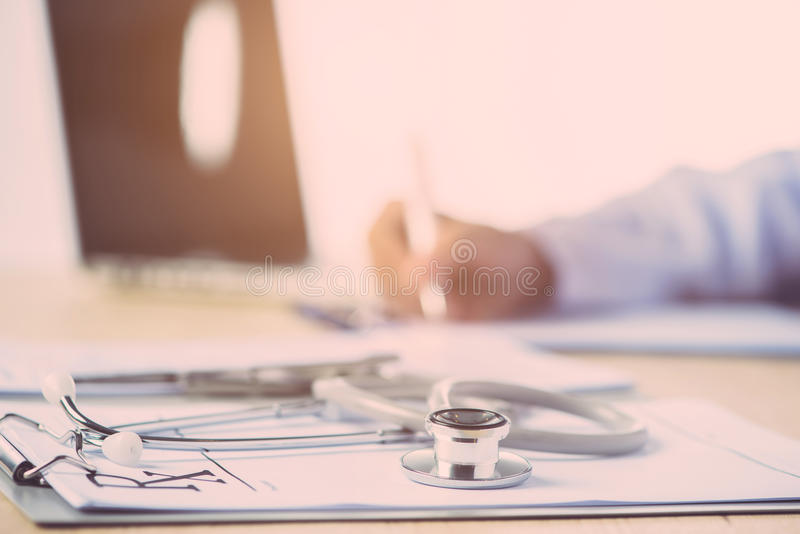 Doctor completing a Medical Claim Form by Stethoscope stock photos